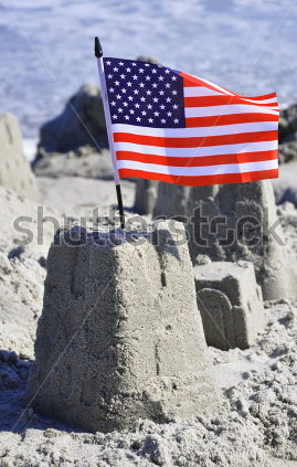 stock-photo-sand-castle-with-american-flag-on-the-beach-64496590